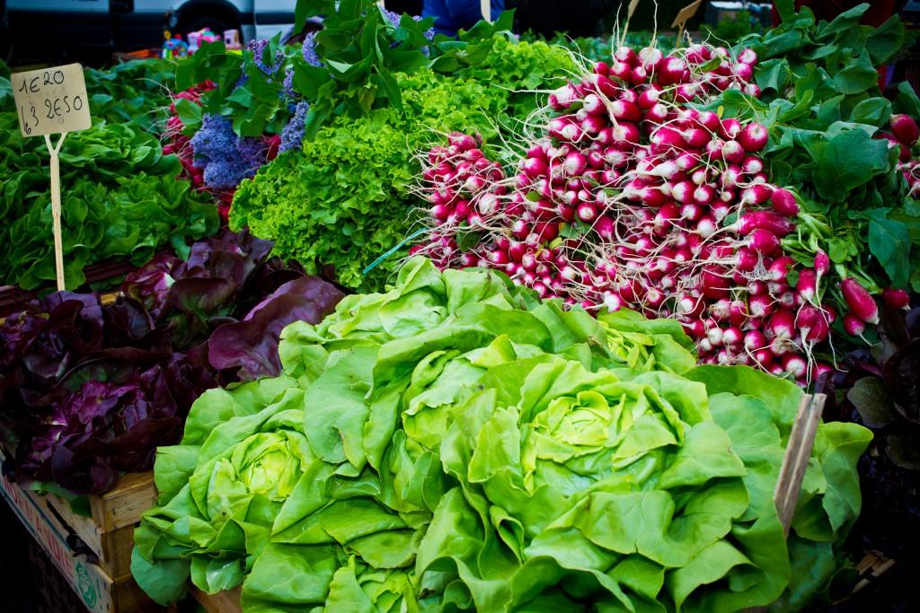 Etal marché avec laitues, radis, salades, et fleurs